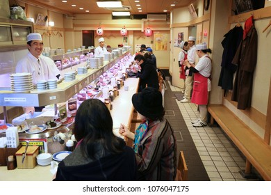 KYOTO, JAPAN - NOVEMBER 27, 2016: Sushi chef prepares sushi in a typical kaitenzushi style (conveyor belt sushi) Japanese restaurant in Kyoto.