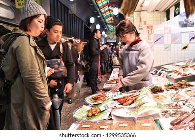 KYOTO, JAPAN - NOVEMBER 27, 2016: People shop at Nishiki Market in Kyoto, Japan. Nishiki is a popular traditional food market in Kyoto.