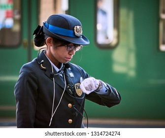 Kyoto / Japan - November 3, 2017: Female train station officer checking the time in Kyoto station, Kyoto, Japan
