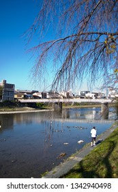 Kyoto, Japan - November 30, 2013: Man jogging along Kamogawa river on a sunny autumn day