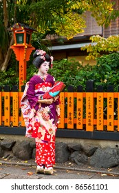 KYOTO, JAPAN - NOVEMBER 8: An unidentified young Maiko stands on Shinbashi street in the Gion district on November 8, 2010 in Kyoto, Japan. Maiko is the title given to an apprentice Geisha.