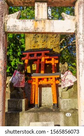 Kyoto, Japan - October 10, 2019: View of a Torii gate, and a fox (Kitsune) figure, on the Inari mountain, in Kyoto, Japan