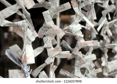 KYOTO, JAPAN - OCTOBER 17, 2018: Soft focus of japanese omikuji fortune paper tied on a line in a temple.