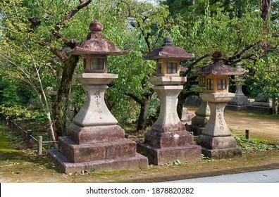 KYOTO, JAPAN - OCTOBER 17, 2019:  The view of the three kaku-doro traditional stone square lanterns along the footpath at the Kitano Tenmangu shrine. Kyoto. Japan