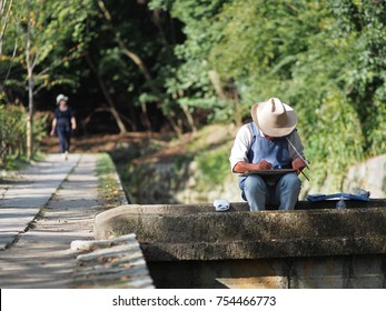 Kyoto, Japan - September 30, 2013: A man sits on a bridge and paints the surrounding scenery at the famous Philosoper's Walk - also known as Philosopher's Path - in Kyoto, Japan.