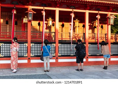 Kyoto, Japan - September 5, 2018: Asian woman dressing kimono and other people praying for bless in the temple Fushimi inari shrine, Kyoto, Japan.