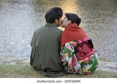 KYOTO, JAPAN-NOVEMBER 4, 2014;Young Japanese adult couple, both in kimono, kissing at the border of the Kamo river.November 4, 2014 Kyoto, Japan