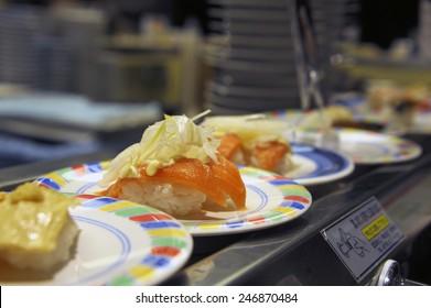 Kyoto, Japan-November 5, 2014; salmon sushi at a conveyor belt at a cheap sushi restaurant. Selective focus at the salmon sushi.November 5, 2014 Kyoto, Japan