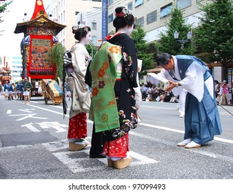 KYOTO - JULY 17: Two geishas receive a gift from a participant of the famous annual Gion Festival held on July 17 2010 in Kyoto, Japan. Geishas often participate in traditional celebrations.