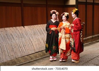 KYOTO - NOV 21: Unidentified Geishas walking by an old street and speaking on November 16, 2010 in Gion district, Kyoto, Japan. Geishas are girls skilled in traditional japanese arts.
