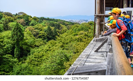 Kyoto, Kyoto prefecture / Japan - 05 12 2018: Young Japanese first graders with yellow caps look down from the balcony of Kiyomizu-dera temple in Kyoto.
