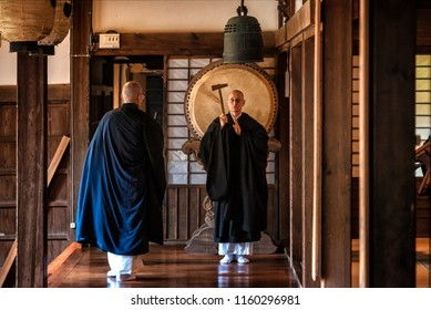 KYOTO PREFECTURE, JAPAN - NOVEMBER 18, 2015: Buddhist monk is ringing drama gong for ceremony at the temple in Kyoto Prefecture, Japan.