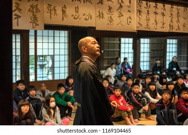 KYOTO PREFECTURE, JAPAN - NOVEMBER 18, 2015: Japanese monk is teaching about buddhism to school kids at the temple in Kyoto, Japan.