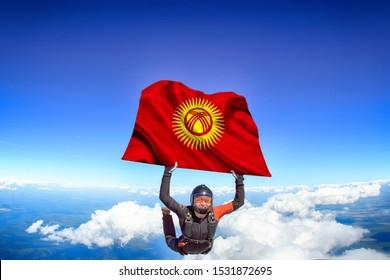 Kyrgyzstan. Flag in skydiving. People in free fall grab flag of Kyrgyzstan. Patriotism, men and flag.