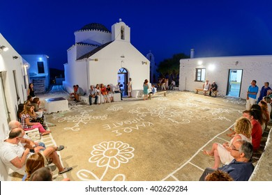 KYTHNOS, GREECE - AUGUST 14, 2014: People waiting for the Assumption eve liturgy to commence at the church of Panagia Stratolatissa