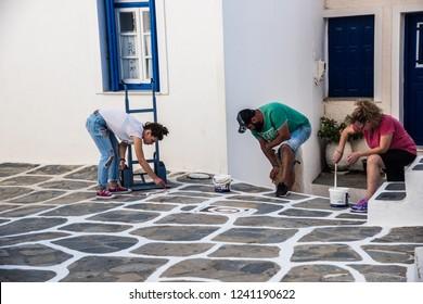 Kythnos, Greece -- September 23, 2018 : People painting streets of Chora village, Kythnos, Greece