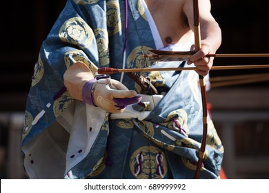 Kyudo, the way of the bow or Japanese Archery. Bowman wearing traditional clothes and gloves getting ready.