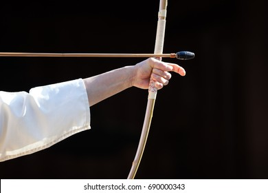 Kyudo, the way of the bow or Japanese Archery. Bow-woman stretching a bow and being ready to fire.