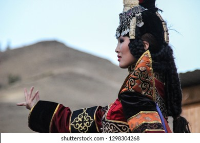 Kyzyl, Tyva, Russia - August 10, 2014: Mongolian woman in shaman and witch costume dances on stage in the mountains. Tyva folk dances