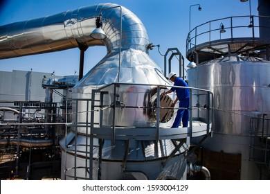 Kzylorda region/Kazakhstan - April 30 2012: Sulfuric acid plant. Furnace for burning sulfur to sulphur dioxide. Maintenance worker in blue work wear on metal platform