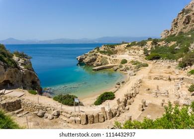 Τhe L- shaped stoa and a beautiful small beach beneath at archaeological site of Heraion, sanctuary of goddess Hera, in Perachora, Loutraki, Greece
