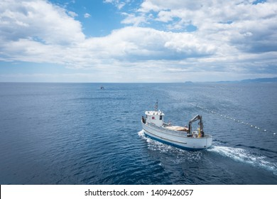 LA AZOHIA, CARTAGENA, MURCIA SPAIN - MAY 25, 2019: Aerial view fishing boat leaving to work in Almadraba. Drone shot