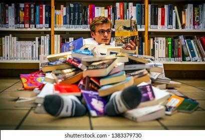 La Louvière, Belgium - October 31, 2018:  Teenager boy reading a book under a big pile of books in a library at Bibliothèque Provinciale de la Louvière in Belgium