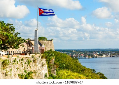 La Cabana spanish fortress walls and cuban flag in th foreground, with sea in the background, Havana, Cuba
