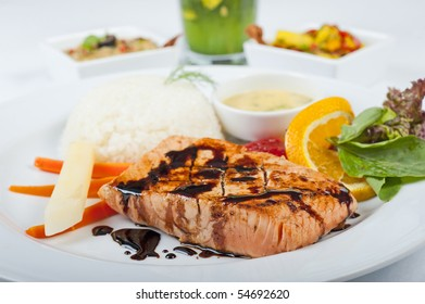 A la carte salmon steak meal on a white plate with salad and rice