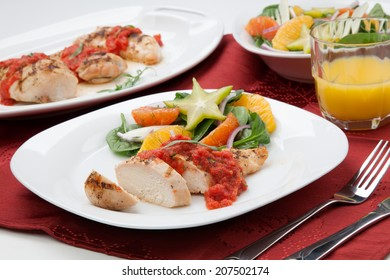 A la carte served grilled chicken breast with spinach - citrus salad served with fresh tomato tarragon sauce and orange juice.