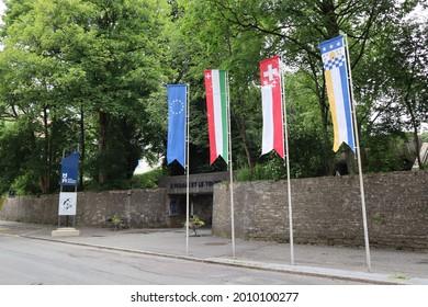 La Chaux-de-Fonds, Switzerland - 7.14.2021: Flags of Switzerland, Neuchatel, Europe and La Chaux-de-Fonds flying near the street entrance and walls of the International Watchmaking Museum.