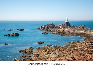 La Corbiere lighthouse and causeway at low tide with the seabed and rocks in the foreground. The image was taken on a clear summer day.