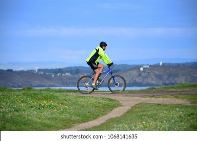 LA CORUNA, SPAIN - APRIL 01, 2018: Unknown man riding a bike on TheField of the Rat. It is an extension of land, located very close to theTower of Herculesand near the beach of Adormideras.