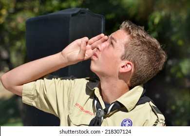 LA CRESCENTA, CA - SEPTEMBER 13, 2014: A Boy Scout looks upward right to left and salutes during a 9/11 memorial held on September 13, 2014 in La Crescenta, California.