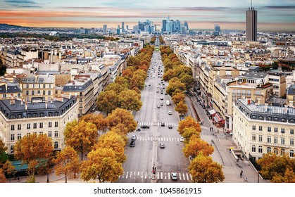 La Defense Financial District Paris France in autumn. Traffic on Champs-Elysees with orange and yellow trees aside.