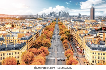La Defense Financial District Paris France in autumn. Traffic on Champs-Elysees. Trees with orange and yellow leafs.