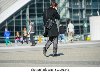 La defense, France- April 09, 2014: side view of businessman walking in a street by phoning. He wears shoulder strap bag