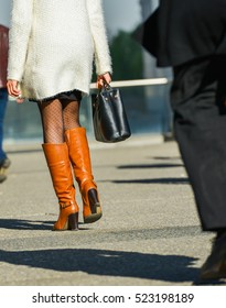 La defense, France- April 10, 2014:portrait of a business woman walking with bag on a street. She wears short skirt and elegant brown tall boots. followed closely by man who could be a sexual predator
