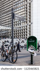 La Defense, France- April 19th, 2012: Image of a bicycle near a pole and a newpapers box, in front of people walking in the Grand Arche area in La Defense, the main business district of Paris.