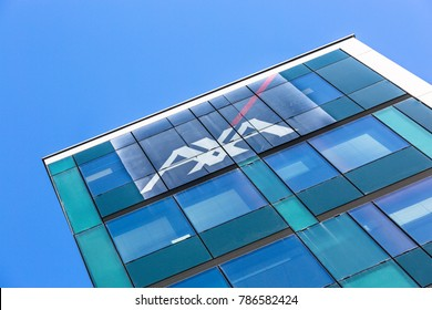 La defense, France - May 10 2015: Axa logo on face of modern building under blue sky. Axa is a French insurance and bank services company