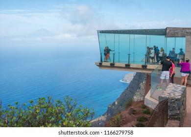 La Gomera, Canary islands - september 18, 2016: Mirador de Abrante with glass walls on the mountains overlooking the landscapes and town of Agulo with the island of Tenerife in the background