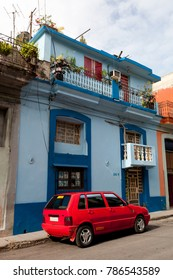 LA HAVANA, CUBA - 3th of June 2015: red car parked in the street in front of a blue facade house by a sunny day