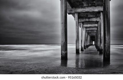 La Jolla beach, California,  long exposure under the pylons, black and white image.