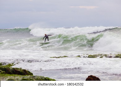 LA JOLLA, CA - JANUARY 30, 2014: Unknown surfer riding a big wave during a surf session in La Jolla California.