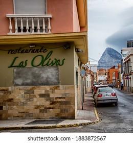 La Linea de la Concepcion, Cadiz, Spain. October 10 2019. Street corner in a Spanish city. Gibraltar rock in the background. Restaurant Las Olivas sign on the wall.