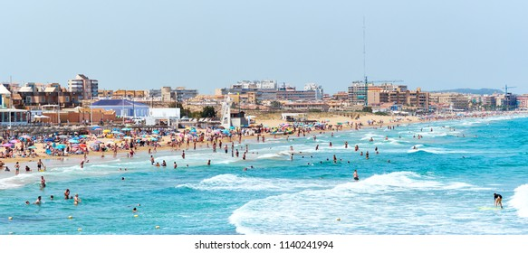 La Mata, Spain - June 25, 2018: Crowd of people sunbathing and swimming on La Mata beach at summer. Tourists and vacationers enjoying the Mediterranean Sea. High season. Torrevieja. Costa Blanca Spain