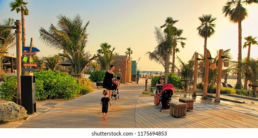 La Mer in Dubai, UAE - May 06, 2018: A woman with a child is walking along the promenade on La Mer's beach.  It is a new beachfront district with shopping and restaurants in Jumeirah.