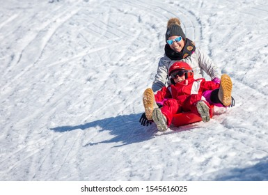 La Mongie, France - March 21, 2019:Excited woman and boy in winter outwear smiling while riding sled on snowy mountain slope on sunny day on ski resort