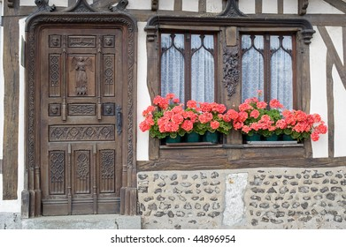 La Neuville-Chant-d'Oisel (Seine-Maritime, Haute Normandie, France) - Exterior of old half-timbered house with red flowers at window
