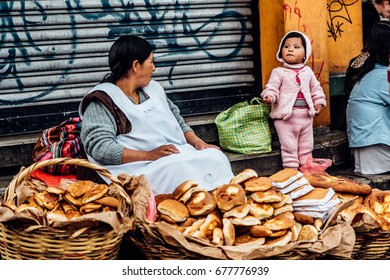 La Paz, Bolivia, 18th, Jan, 2016: A mother is staring at her little girl when selling bread by the street in the capital of Bolivia.